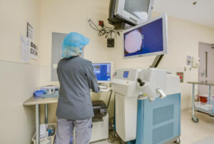 Nurse stadning at optical laser with various equipment in the room