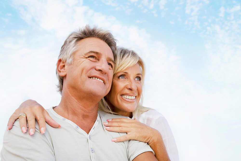 Happy older couple embracing with bright, blue sky behind them