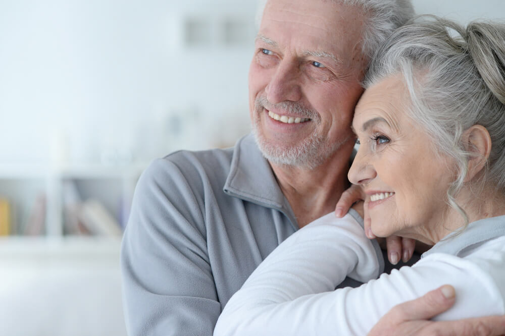 Happy older couple embracing inside their home