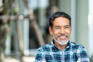 Older man with greying beard smiling outside