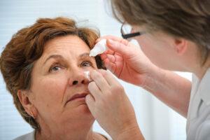 Nurse giving woman eye drops