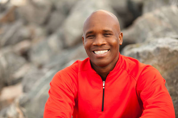 Smiling, in shape man outside with rocks in the background