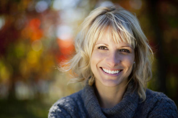 Smiling woman with blonde hair outside with colorful leaves in the background